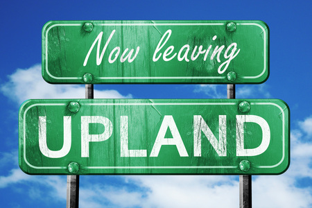 upland: Now leaving upland road sign with blue sky Stock Photo