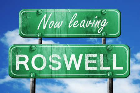 roswell: Now leaving roswell road sign with blue sky Stock Photo