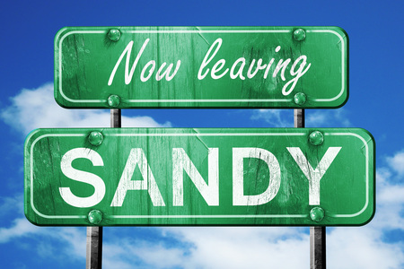sandy: Now leaving sandy road sign with blue sky