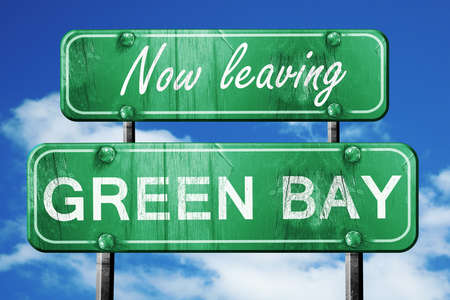 going green: Now leaving green bay road sign with blue sky