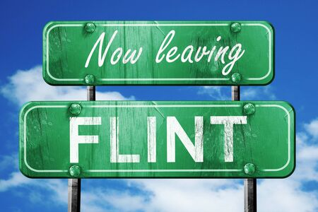 leaving: Now leaving flint road sign with blue sky Stock Photo