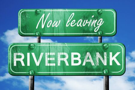 leaving: Now leaving riverbank road sign with blue sky Stock Photo