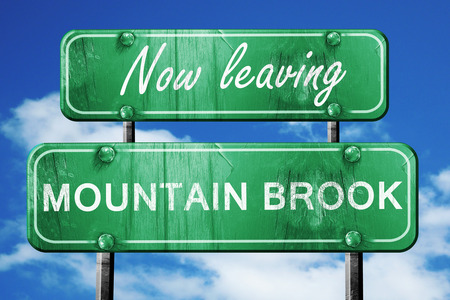 brook: Now leaving mountain brook road sign with blue sky Stock Photo