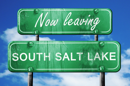 leaving: Now leaving south salt lake road sign with blue sky Stock Photo