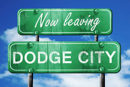 dodge: Now leaving dodge city road sign with blue sky Stock Photo