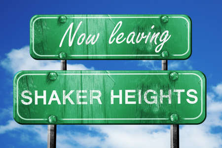 heights: Now leaving shaker heights road sign with blue sky Stock Photo