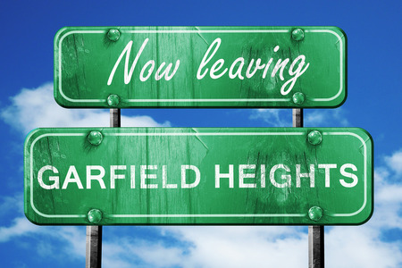 heights: Now leaving garfield heights road sign with blue sky Stock Photo