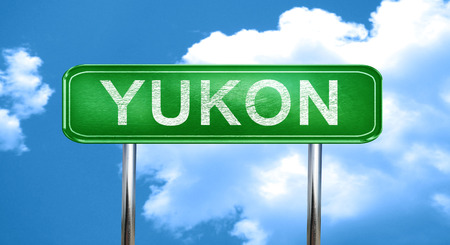 yukon: yukon city, green road sign on a blue background