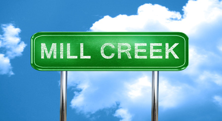 brook: mill creek city, green road sign on a blue background Stock Photo