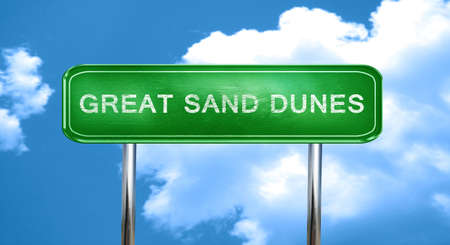 sand dunes: Great sand dunes city, green road sign on a blue background Stock Photo