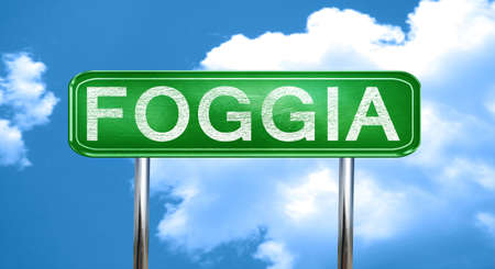 foggia: Foggia city, green road sign on a blue background Stock Photo