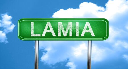 lamia: Lamia city, green road sign on a blue background Stock Photo