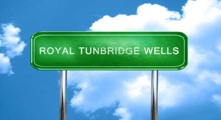 wells: Royal tunbridge wells city, green road sign on a blue background Stock Photo