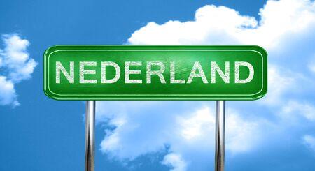 nederland: Nederland city, green road sign on a blue background Stock Photo