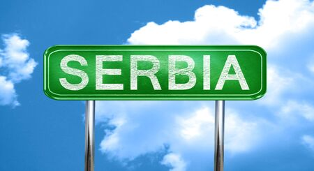 serbia: Serbia city, green road sign on a blue background Stock Photo