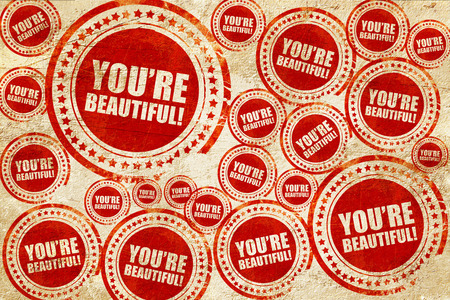 compliment: youre beautiful!, red stamp on a grunge paper texture