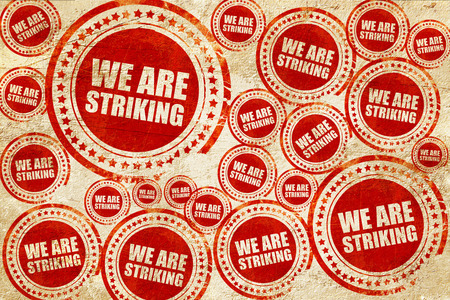 striking: we are striking, red stamp on a grunge paper texture