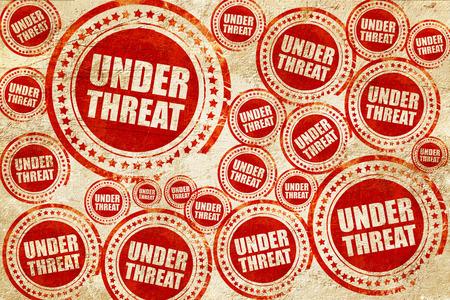 threat: under threat, red stamp on a grunge paper texture Stock Photo