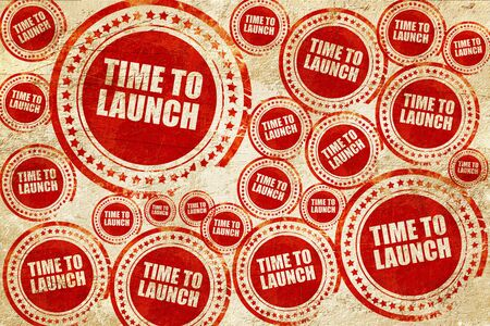 unveil: time to launch, red stamp on a grunge paper texture Stock Photo