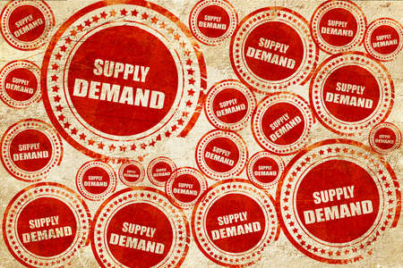 in demand: supply and demand, red stamp on a grunge paper texture