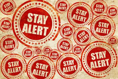 stay alert: stay alert, red stamp on a grunge paper texture