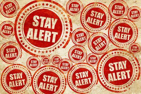 safety slogan: stay alert, red stamp on a grunge paper texture
