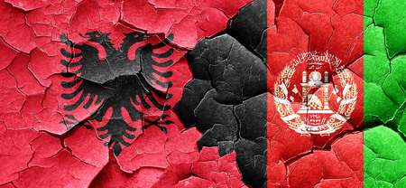 Albania flag with afghanistan flag on a grunge cracked wall