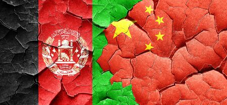 afghanistan flag: Afghanistan flag with China flag on a grunge cracked wall Stock Photo