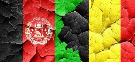 afghan: Afghanistan flag with Belgium flag on a grunge cracked wall