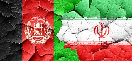 Afghanistan flag with Iran flag on a grunge cracked wall