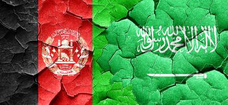 Afghanistan flag with Saudi Arabia flag on a grunge cracked wall