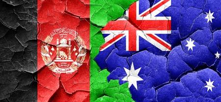 Afghanistan flag with Australia flag on a grunge cracked wall