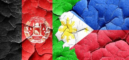 Afghanistan flag with Philippines flag on a grunge cracked wall