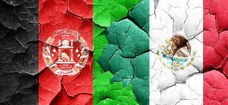 Afghanistan flag with Mexico flag on a grunge cracked wall