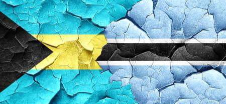 bahamas: Bahamas flag with Botswana flag on a grunge cracked wall Stock Photo