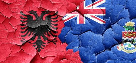 cayman: Albania flag with Cayman islands flag on a grunge cracked wall