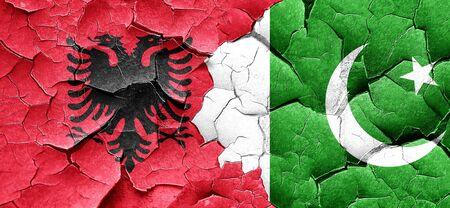 pakistan flag: Albania flag with Pakistan flag on a grunge cracked wall