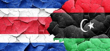 rican: Costa Rica flag with Libya flag on a grunge cracked wall