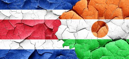 rican: Costa Rica flag with Niger flag on a grunge cracked wall