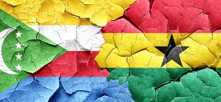 ghanese: Comoros flag with Ghana flag on a grunge cracked wall Stock Photo