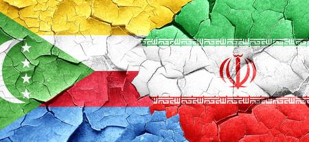 comoros: Comoros flag with Iran flag on a grunge cracked wall