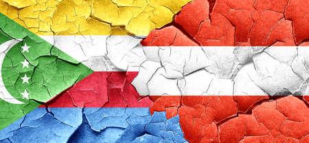 comoros: Comoros flag with Austria flag on a grunge cracked wall
