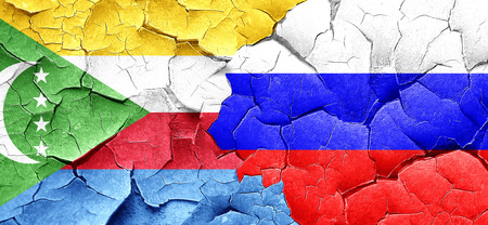 russia flag: Comoros flag with Russia flag on a grunge cracked wall Stock Photo