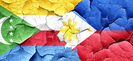 philippino: Comoros flag with Philippines flag on a grunge cracked wall Stock Photo