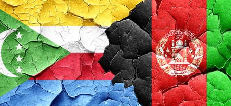 afghanistan flag: Comoros flag with afghanistan flag on a grunge cracked wall Stock Photo
