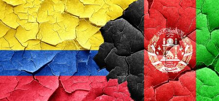 afghanistan: Colombia flag with afghanistan flag on a grunge cracked wall Stock Photo