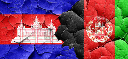 Cambodia flag with afghanistan flag on a grunge cracked wall