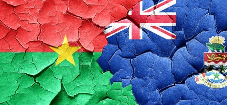 cayman: Burkina Faso flag with Cayman islands flag on a grunge cracked wall