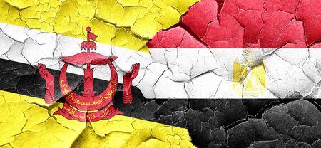 bandera de egipto: bandera de Brunei con la bandera de Egipto en una pared agrietada grunge Foto de archivo