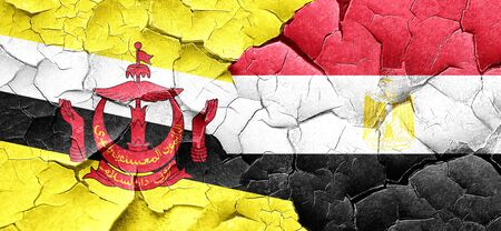 egypt flag: Brunei flag with egypt flag on a grunge cracked wall